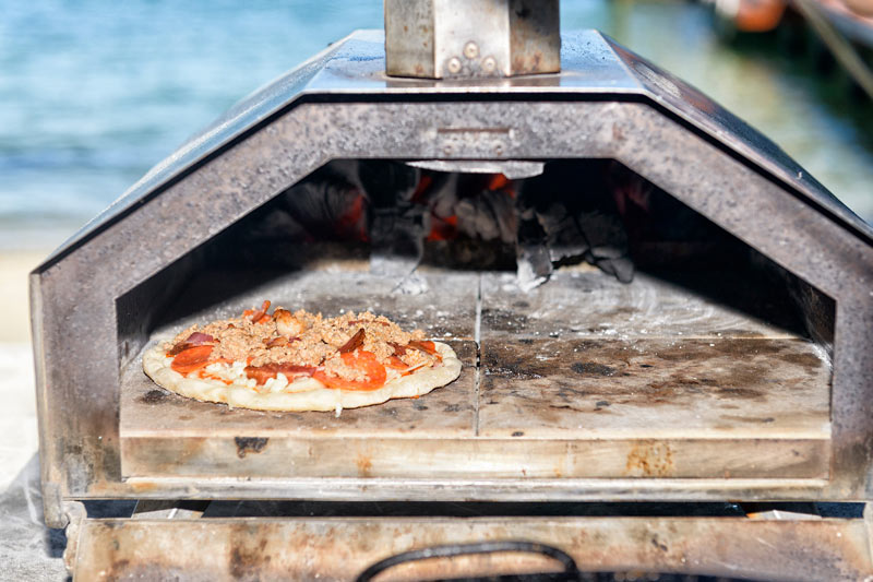 Wood-fired pizza on beach